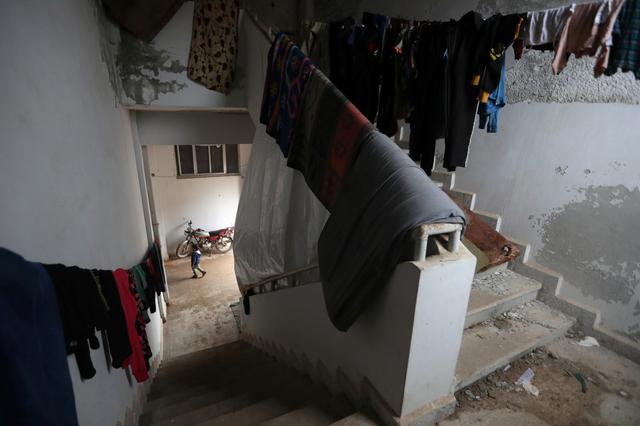 The laundry of Internally displaced people hangs inside an empty school and university compound used as shelter, in Azaz, Syria February 21, 2020.  REUTERS/Khalil Ashawi