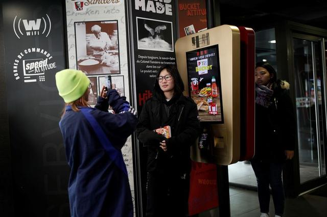 People take pictures in front of a commemorative plaque on the self-ordering kiosk used by celebrity couple?Kim Kardashian?and?Kanye West?at the Strasbourg Saint-Denis branch of the chicken chain KFC in Paris, France, February 21, 2020. REUTERS/Benoit Tessier
