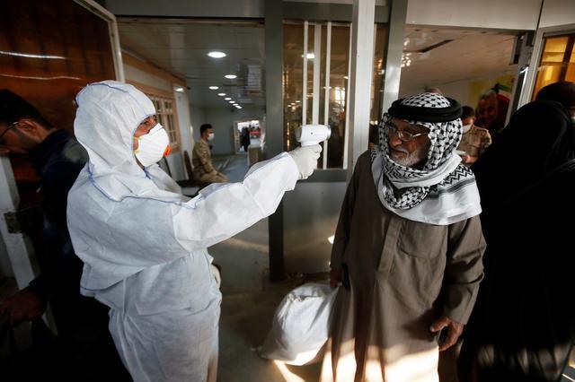 An Iraqi medical staff member checks a passenger's temperature, amid the new coronavirus outbreak, upon his arrival to Shalamcha Border Crossing between Iraq and Iran, February 20, 2020. REUTERS/Essam al-Sudani
