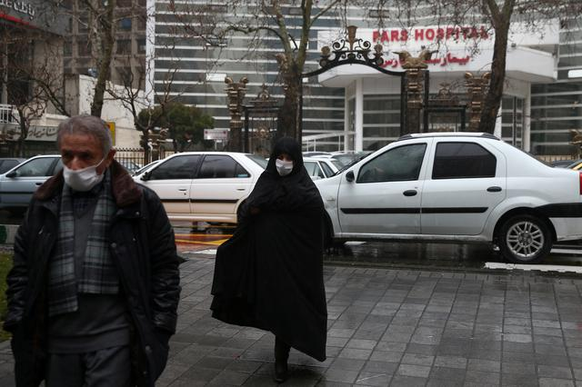 Iranian people wearing protective masks to prevent contracting a coronavirus walk in front of a hospital in Tehran, Iran February 20, 2020. WANA (West Asia News Agency)/Nazanin Tabatabaee via REUTERS