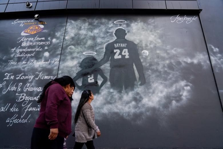 La gente pasa frente a un mural ante el monumento público del gran Kobe Bryant de la NBA, su hija y otras siete personas el 24 de febrero. REUTERS / Kyle Grillot