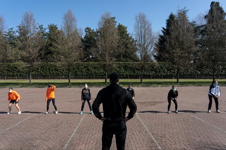 A youth volleyball team trains outside wearing protective masks, with each person one metre apart from each other due to government restrictions, on the 16th day of quarantine in Codogno, March 7. Marzio Toniolo/via REUTERS