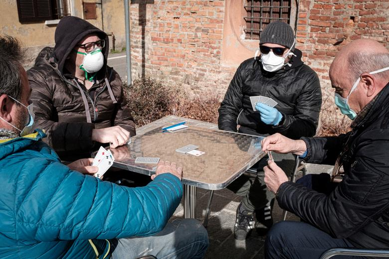 A group of men wearing protective masks play a game of cards out on a street in San Fiorano, February 27. Marzio Toniolo/via REUTERS