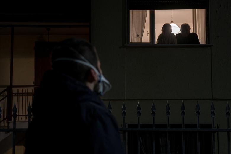 Life inside a red zone: A man wearing a mask looks up at a couple looking out of a window from a house on the 15th day of quarantine in San Fiorano, one of the small towns in northern Italy that has been on lockdown since February, March 6, 2020. Primary school teacher Marzio Toniolo shares images from inside Italy's 'red zone', areas placed under quarantine at the heart of the country's coronavirus outbreak. Marzio Toniolo/via REUTERS