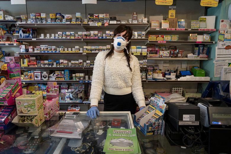 Silvia wears a protective mask as she waits for customers in a tobacconist in San Fiorano, one of the towns on lockdown in northern Italy due to a coronavirus outbreak, March 3. To ease tensions, she plays a game with customers also wearing protective masks - guessing who is hiding behind them. Marzio Toniolo/via REUTERS