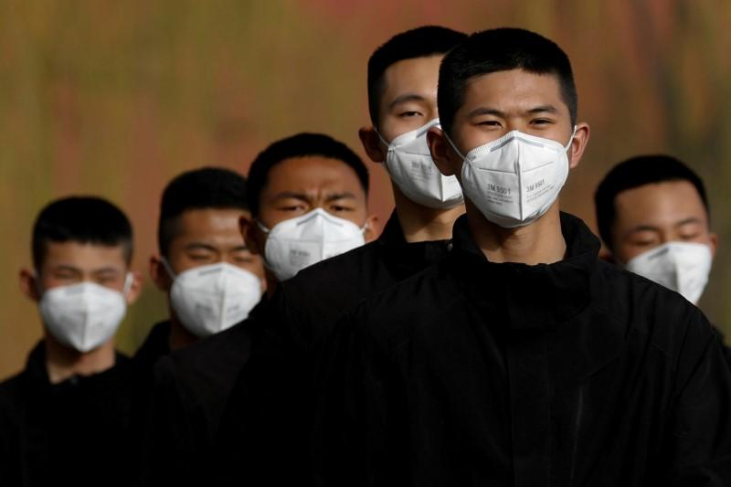 Image result for Security personnel wearing face masks to contain the spread of coronavirus disease (COVID-19) walk along a street outside Forbidden City in Beijing, China March 18, 2020.