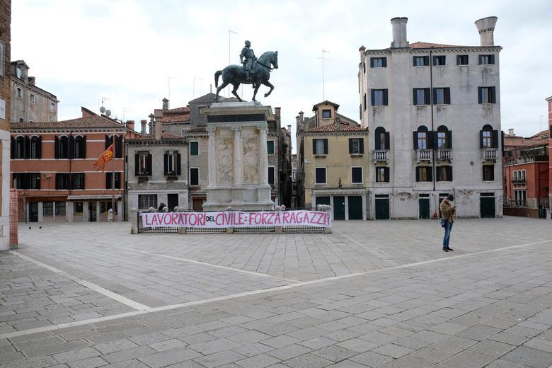 """En el monumento frente a la entrada del hospital veneciano, el 22 de marzo, cuelga una pancarta que dice """"Trabajadores del hospital civil: ¡permanezcan fuertes, muchachos!"""". REUTERS / Manuel Silvestri"""