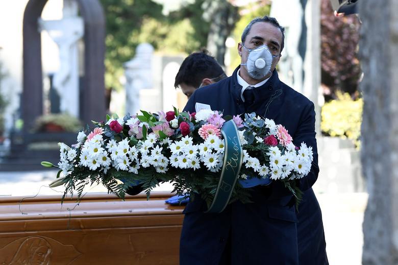 Trabajadores de cementerios y agencias funerarias con máscaras protectoras transportan un ataúd de una persona que murió de coronavirus en Bérgamo, el 16 de marzo. REUTERS / Flavio Lo Scalzo