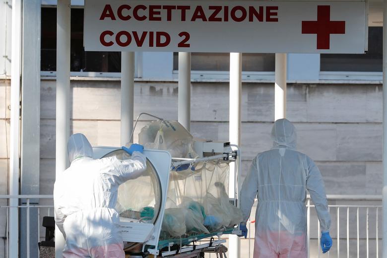 Los trabajadores médicos en trajes protectores empujan una camilla de aislamiento frente a la Clínica Columbus, donde los pacientes que sufren de coronavirus fueron trasladados del Hospital Spallanzani, en Roma, el 16 de marzo. REUTERS / Remo Casilli