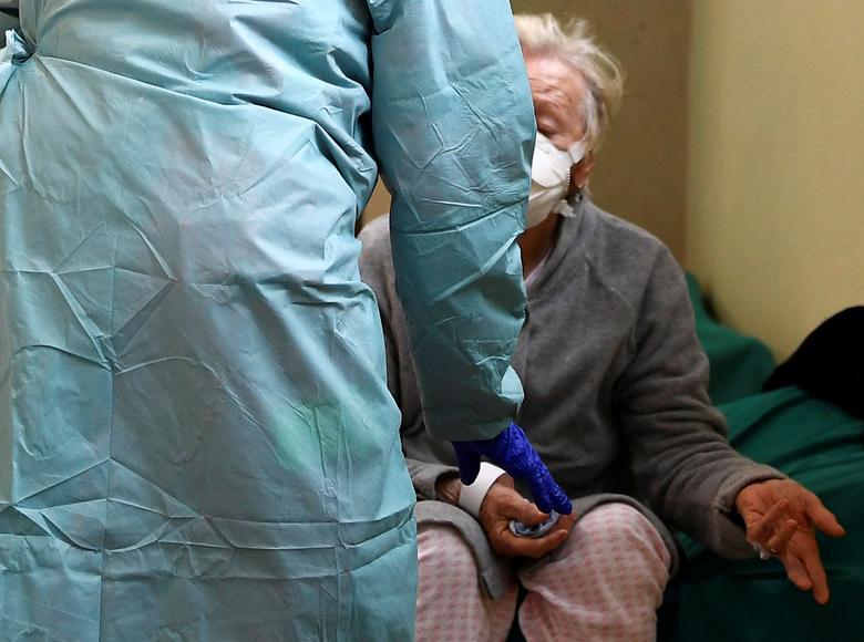 Personal médico ayuda a un paciente dentro del hospital Spedali Civili en Brescia, el 13 de marzo. REUTERS / Flavio Lo Scalzo
