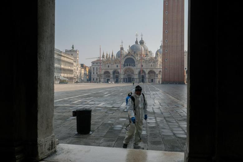 Un trabajador desinfecta la plaza de San Marcos en Venecia, el 12 de marzo. REUTERS / Manuel Silvestri