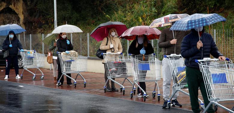 La gente hace cola bajo la lluvia afuera de un supermercado en Catania, el 23 de marzo. REUTERS / Antonio Parrinello