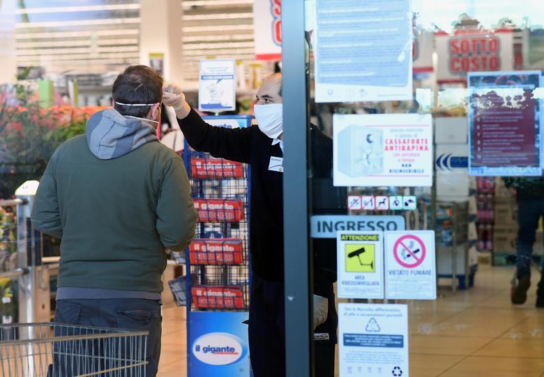 Un empleado comprueba la temperatura de un hombre en la entrada de un supermercado en Milán, el 23 de marzo. REUTERS / Daniele Mascolo