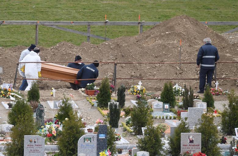 Los trabajadores colocan un ataúd en el suelo en un cementerio en Milán, el 23 de marzo. REUTERS / Daniele Mascolo