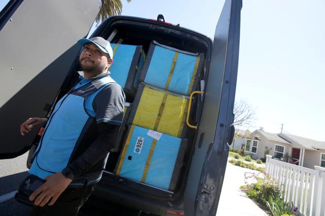 Joseph Alvarado opens the back of the van as he makes deliveries for Amazon during the outbreak of the coronavirus disease (COVID-19) in Costa Mesa, California, U.S., March 23, 2020.      REUTERS/Alex Gallardo