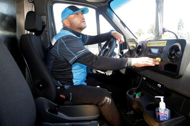 Joseph Alvarado in the driver seat as he makes deliveries for Amazon during the outbreak of the coronavirus disease (COVID-19) in Costa Mesa, California, U.S., March 23, 2020.   REUTERS/Alex Gallardo