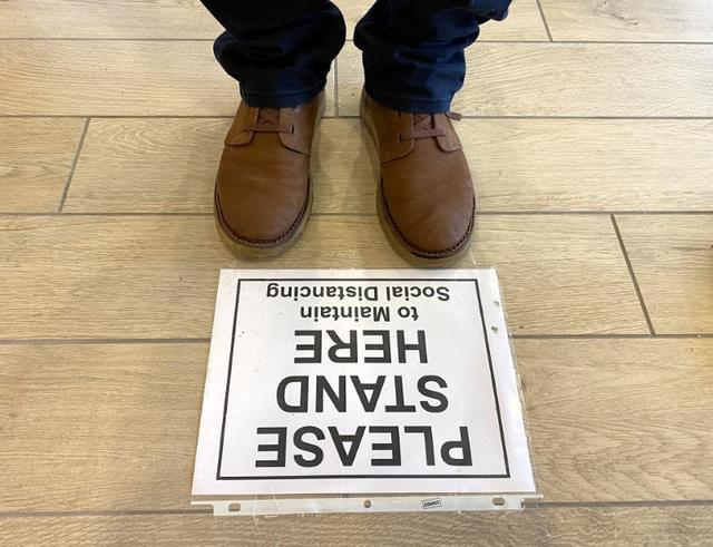 FILE PHOTO: A sign on the floor asks customers to maintain social distancing while on line at a bank to prevent the spread of coronavirus in Falls Church, Virginia, U.S., March 25, 2020. REUTERS/Kevin Lamarque