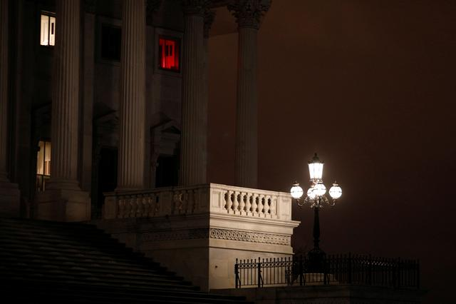 A window illuminated with a red light shines above the U.S. Senate steps, ahead of a vote on the coronavirus (COVID-19) relief bill on Capitol Hill in Washington, U.S., March 25, 2020. REUTERS/Tom Brenner