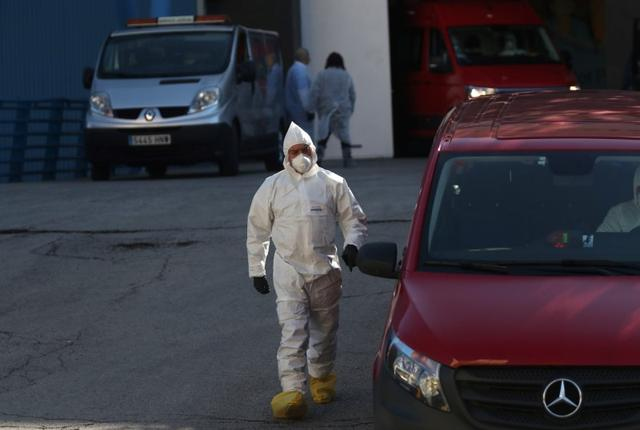 A member of the Spanish army wearing a protective suit stands outside an ice rink, being used as a morgue, during the coronavirus disease (COVID-19) outbreak in Madrid, Spain, March 26, 2020. REUTERS/Susana Vera