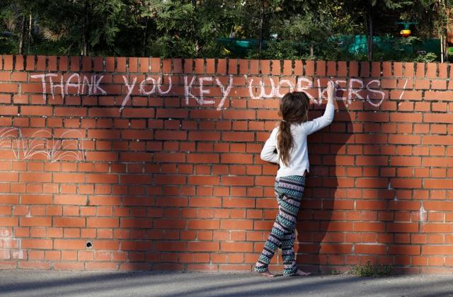 A girl writes a message in support of key workers, as the spread of the coronavirus disease (COVID-19) continues, High Wycombe, Britain, March 26, 2020. REUTERS/Eddie Keogh