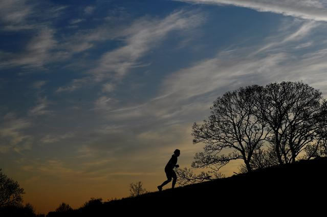 A woman runs on Primose Hill at dusk, as the spread of the coronavirus disease (COVID-19) continues, London, Britain, March 26, 2020. REUTERS/Toby Melville