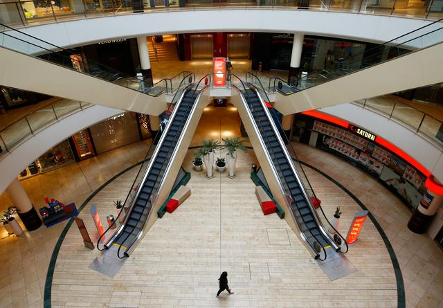 FILE PHOTO: A person is seen inside an empty shopping mall during a partial lockdown in Leverkusen, Germany, March 20, 2020, as the spread of the coronavirus disease (COVID-19) continues. REUTERS/Thilo Schmuelgen/File Photo