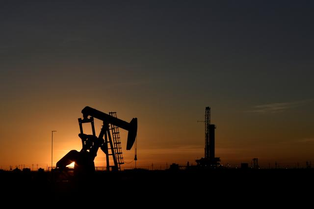 FILE PHOTO: A pump jack operates in front of a drilling rig at sunset in an oil field in Midland, Texas U.S. August 22, 2018. REUTERS/Nick Oxford