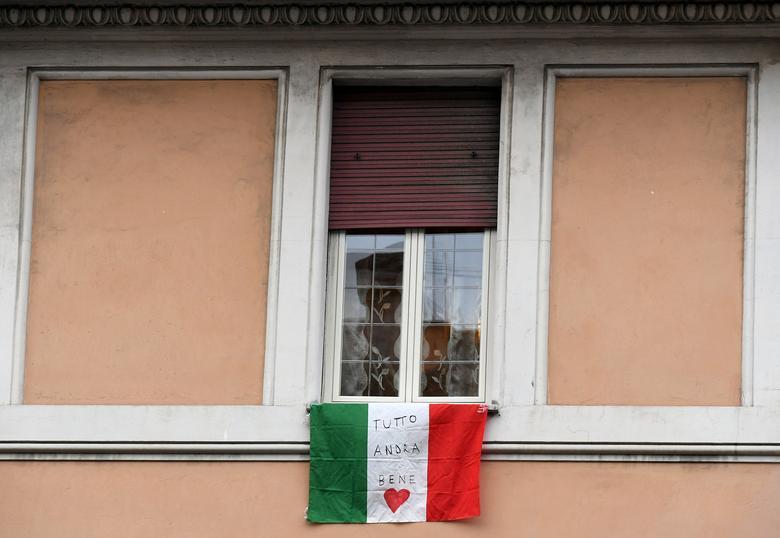 Італійський прапор висить на балконі квартири з написом «Tutto andra bene» - «все буде добре», фраза, яка стала символом надії в італійському кризу з коронавірусів, як частина флешмобу, організованого для підняття морального духу в Римі, Італія, березень 13, 2020 . REUTERS / Alberto Lingria