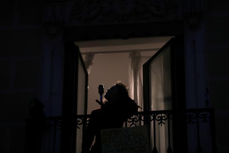 """Іспанська блюзова співачка Беатріс Беродах """"Бетта"""" співає зі свого балкона під час щоденного вечірнього концерту, щоб підтримати працівників охорони здоров'я і полегшити сусідам перенесення блокування на коронавірус в Мадриді, Іспанія, 19 березня 2020 року. REUTERS / Susana Vera"""