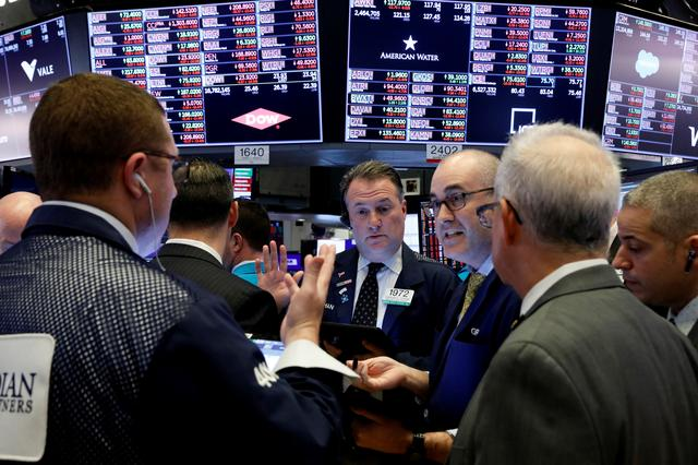 FILE PHOTO: Traders work on the floor of the New York Stock Exchange (NYSE) near the close of trading in New York, U.S., March 12, 2020. REUTERS/Brendan McDermid