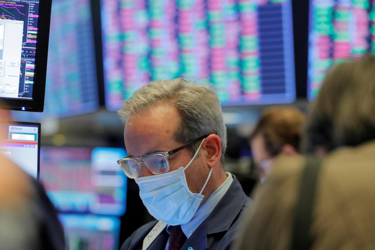 FILE PHOTO: A trader wears a mask as he works on the floor of the New York Stock Exchange (NYSE) as the building prepares to close indefinitely due to the coronavirus disease (COVID-19) outbreak in New York, U.S., March 20, 2020. REUTERS/Lucas Jackson