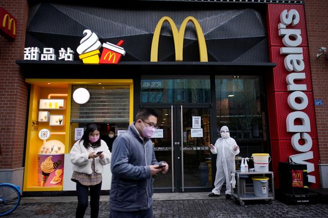 People wearing face masks are seen outside a McDonald's restaurant in Wuhan, Hubei province, the epicentre of China's coronavirus disease (COVID-19) outbreak, March 30, 2020.  REUTERS/Aly Song