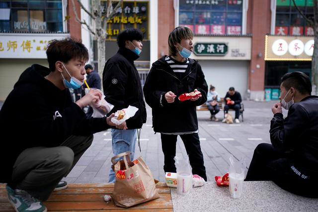 People with face masks eat outside a McDonald's restaurant in Wuhan, Hubei province, the epicentre of China's coronavirus disease (COVID-19) outbreak, March 30, 2020.  REUTERS/Aly Song