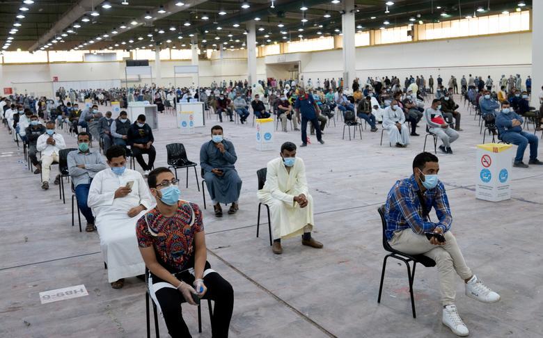 Экспатрианты ждут обязательного тестирования на коронавирус в импровизированном центре тестирования в Мишрефе, Кувейт, 14 марта. REUTERS / Stephanie McGehee