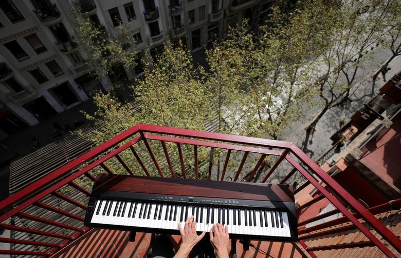 O pianista amador Alberto Gestoso Arce, 37 anos, toca de sua varanda para vizinhos perto da Basílica da Sagrada Família em Barcelona, Espanha, em 21 de março de 2020. REUTERS / Nacho Doce