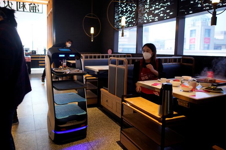 Робот доставляет еду для посетителей в ресторан после вспышки новой коронавирусной болезни (COVID-19) в Шанхае, Китай, 19 марта 2020 года. REUTERS / Aly Song