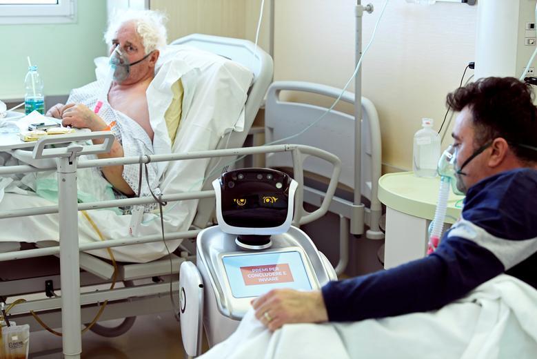 Пациент взаимодействует с роботом, помогая медицинским бригадам лечить пациентов, страдающих коронавирусной болезнью (COVID-19), в больнице Circolo в Варезе, Италия, 1 апреля 2020 года. REUTERS / Flavio Lo Scalzo