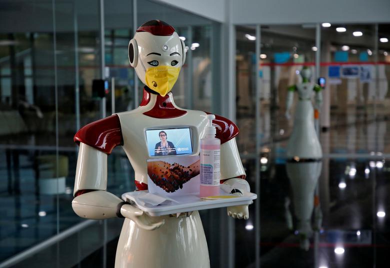 Робот, разработанный начинающей фирмой Asimov Robotics, держит поднос с масками для лица и дезинфицирующим средством после запуска двух роботов для распространения информации о коронавирусе в Кочи, Индия, 17 марта 2020 года. REUTERS / Sivaram V