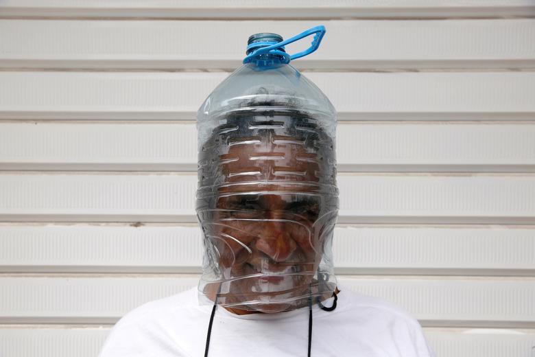 Чоловік демонструє свою саморобну маску перед репатріаційної рейсами в Канаду, організованими канадським посольством для громадян, які опинилися в Перу, в Лімі, 4 квітня 2020 року. РЕЙТЕР / Себастьян Кастанеда