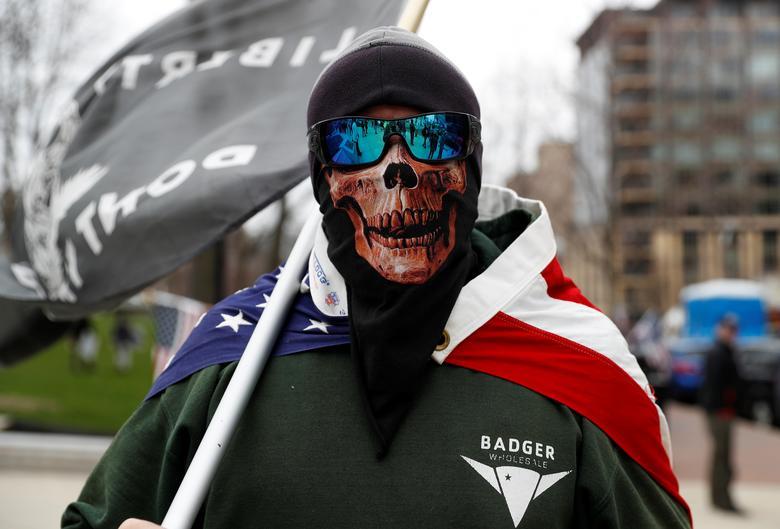 Чоловік в масці вдає з себе демонстрантів, які протестують проти продовження надзвичайного наказу губернатора штату Тоні Еверса «Безпечний на дому» біля будівлі Капітолію в Медісоні, штат Вісконсін, 24 квітня 2020 року. REUTERS / Shannon Stapleton