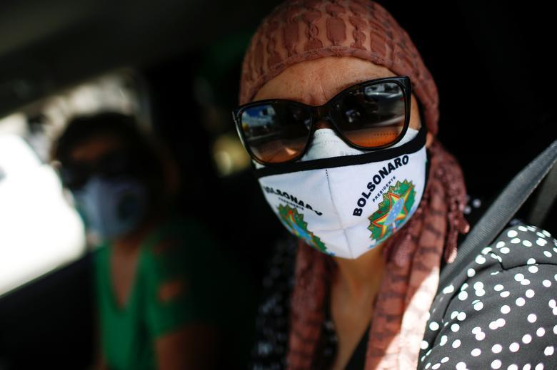 Демонстрант в захисній масці бере участь в автоколоні в знак протесту проти президента Бразилії Жаіра Больсонаро в Бразиліа, Бразилія, 26 квітня 2020 року. РЕЙТЕР / Адріано Мачадо