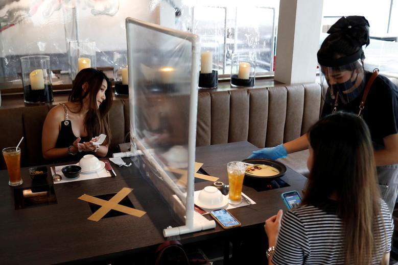 В Бангкоке, Таиланд, 4 мая. Люди обедают в тайваньском ресторане в стиле «горячий горшок», который вновь открылся после ослабления ограничений, связанных с введением пластикового барьера и мер по социальному дистанцированию. REUTERS / Jorge Silva & nbsp;