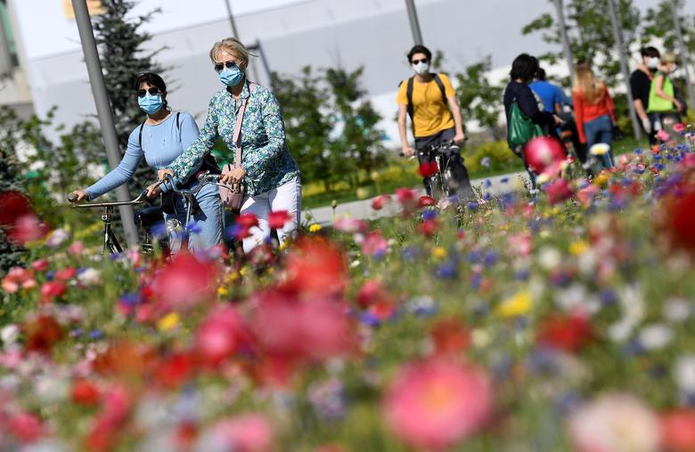 Женщины в защитных масках гуляют со своими велосипедами в парке в районе Порта Нуова, в Милане, Италия, 4 мая. РЕЙТЕР / Флавио Ло Скальцо