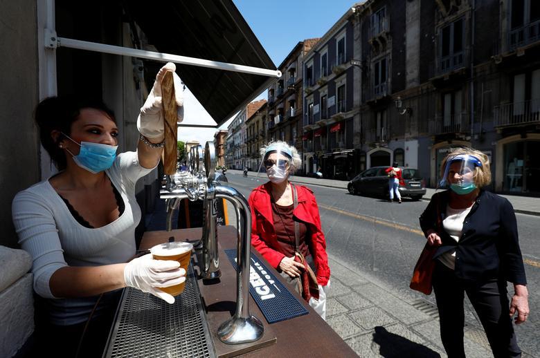 Женщина в маске наливает пиво из-под крана, когда Италия начинает поэтапное завершение общенациональной блокировки в Катании 4 мая. РЕЙТЕР / Антонио Парринелло