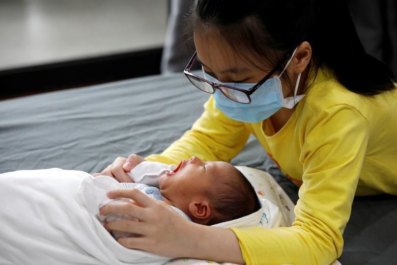 Ха Лінь Нгуєн в захисній масці доглядає за своїм новонародженим братом Фук Аном будинку в Ханої, В'єтнам, 13 квітня 2020 року. REUTERS / Kham