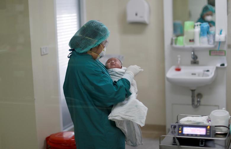 Медсестра тримає місячного тайського дитини, наймолодшого пацієнта COVID-19 в країні, який успішно одужав за день до виписки з Інституту інфекційних захворювань Бамраснарадура в Бангкоку, Таїланд, 22 квітня 2020 року. REUTERS / Jorge Silva
