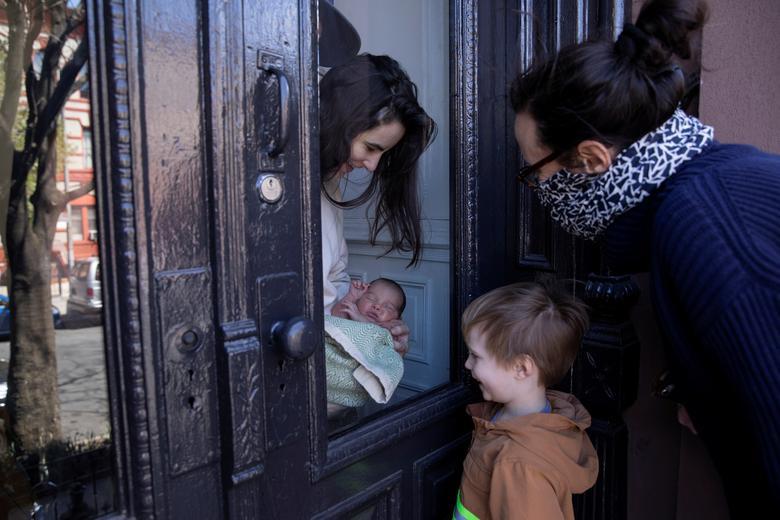 Наомі Хассебрук і її син Фелікс дивляться на новонароджену дитину своєї сестри через скляні двері, кидаючи сумку з припасами на Великодню неділю в Брукліні, Нью-Йорк, 11 квітня 2020 року. REUTERS / Caitlin Ochs