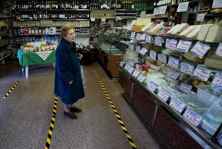 Дама чекає, коли її обслужать за жовтою лінією, що позначає відстань, яке клієнти повинні розділити, в Римі, Італія, 10 березня. REUTERS / Guglielmo Mangiapane