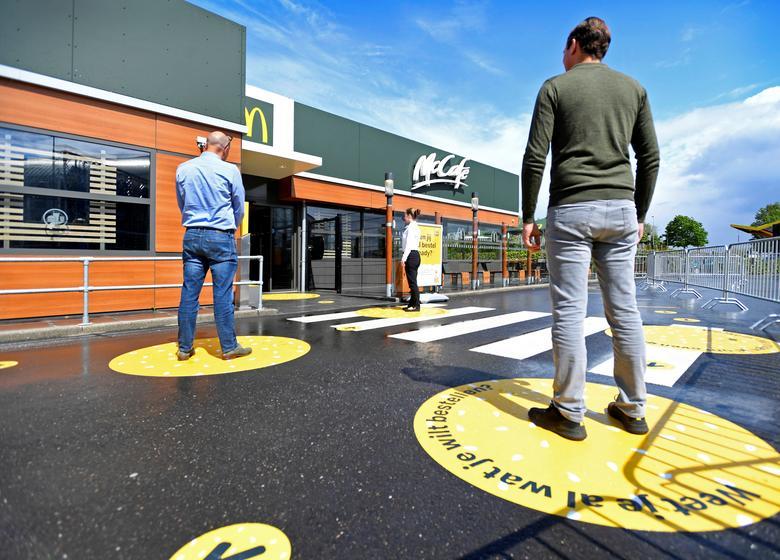 Клієнти чекають зовні на марках соціального дистанціювання в місці прототипу McDonald's в Арнемі, Нідерланди, 1 травня. REUTERS / Piroschka van de Wouw