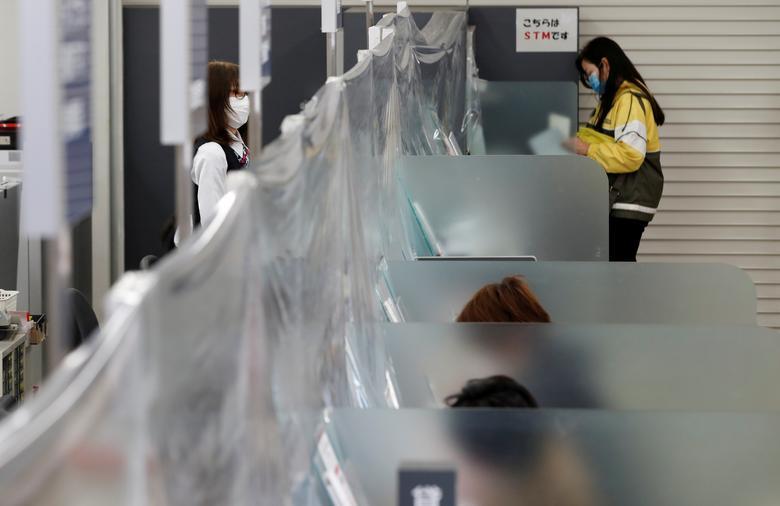 Банківський касир в захисній масці стоїть біля стійки з пластикової шторкою, встановленої для запобігання поширенню коронавируса, у відділенні Хігашінакано MUFG Bank в Токіо, Японія, 24 квітня. REUTERS / Kim Kyung-Hoon